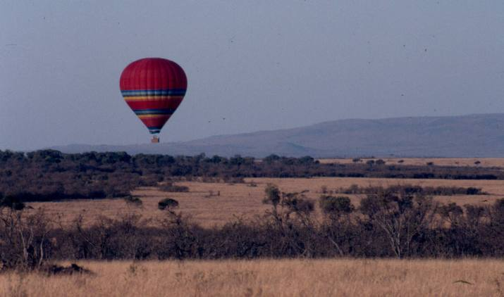 A hot air baloon flies over a rather dry Maasai Mara.